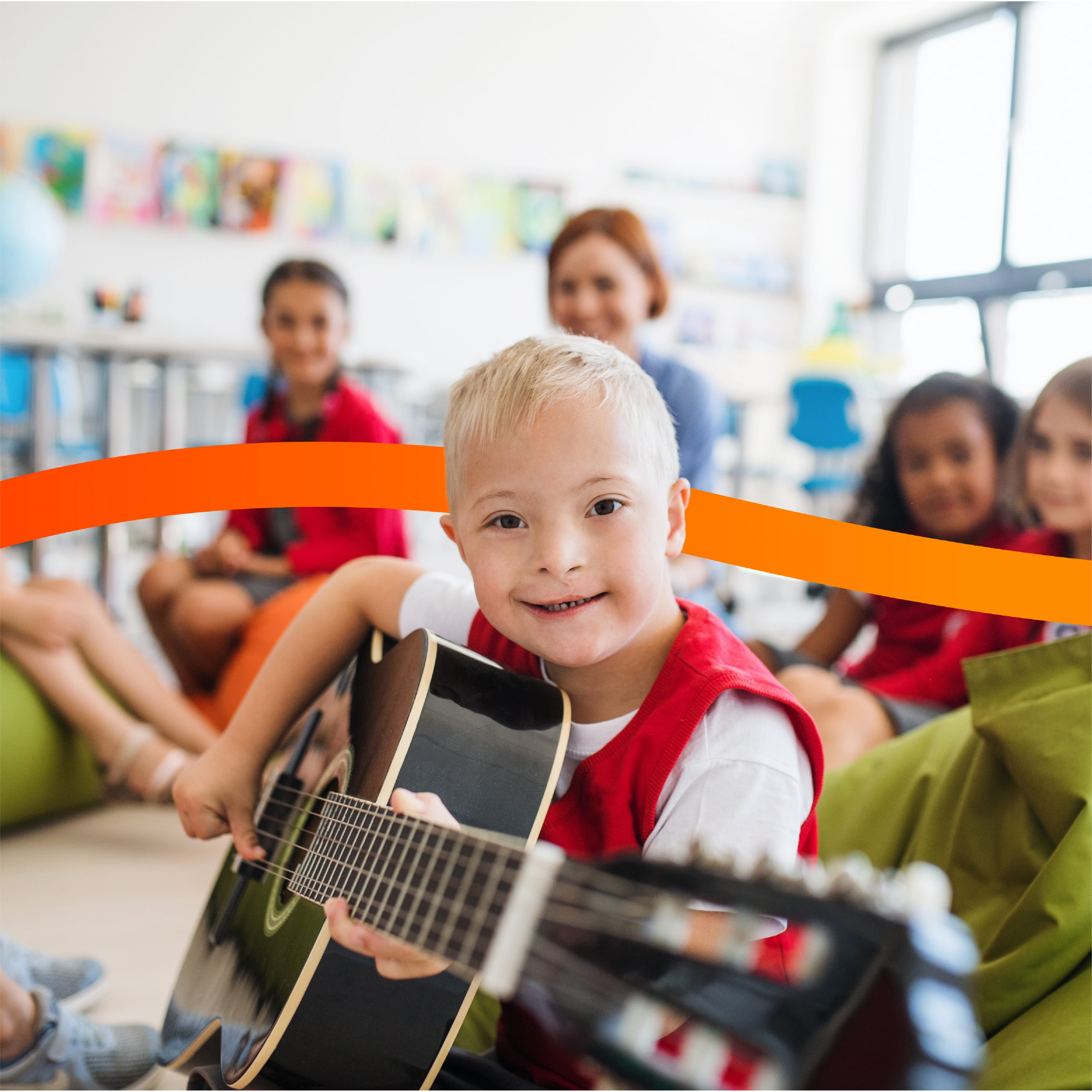 Young boy Down's syndrome playing guitar with other children and teacher in the background