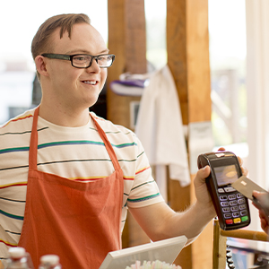 Young man with disability working as shop attendant