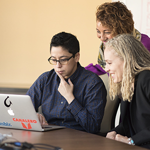 Group of 3 women looking at a latptop screen and smiling