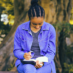 Young woman on park bench writing on her journal