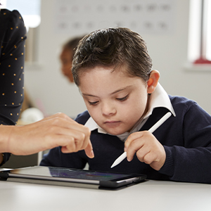 Young boy with Down's syndrome learning on an Ipad with his teacher
